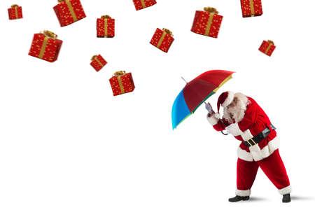generosidad: Santa Claus está protegido por los regalos con el paraguas