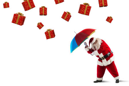 Santa claus is protected by gifts with umbrella