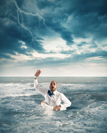 Businessman drowning in the sea and asks for help Stock Photo