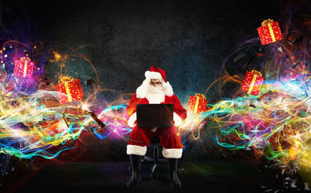 traditional: Santa Claus with a laptop and gift packs on background