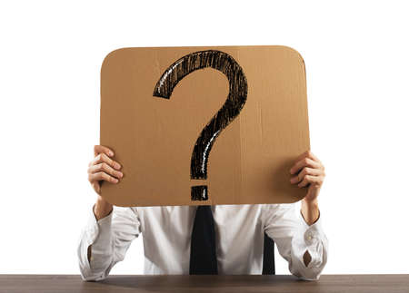 semblance: Businessman in the office holds a cardboard with big question mark Stock Photo