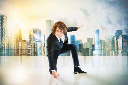 ambitious: Business man punch with power and determination in the floor of roof Stock Photo