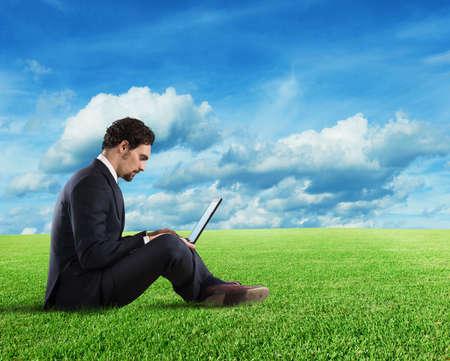 gente comunicandose: Hombre de negocios sentado en un césped de hierba. Internet y el concepto de red social