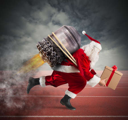 Santa Claus with gift box runs with a missile in a track Stock Photo