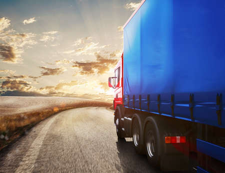 Blue truck on the road with the landscape at sunset  . 3D Rendering Banco de Imagens