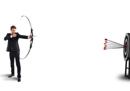 弓と矢を持ったビジネスマンがターゲットをヒットします。 写真素材