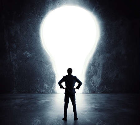large: Businessman looks at a big hole in the shape of a light bulb on the wall