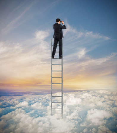 Man op een ladder hoog in de hemel te kijken met een verrekijker Stockfoto