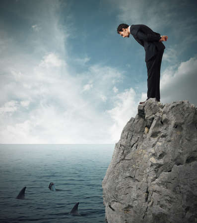 Businessman watching from a cliff the sea with sharks