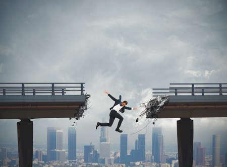 impediment: Businessman falls by jumping a broken bridge. crisis concept