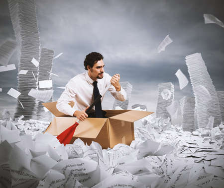 Concept of bureaucracy with man paddling in a sea of sheets Stok Fotoğraf
