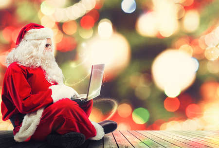 Santa Claus with a laptop and xmas tree on background