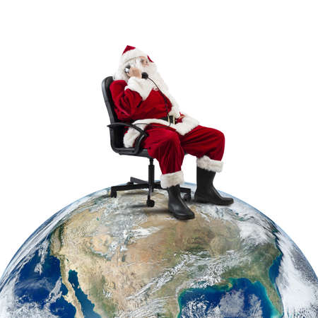 christmas gift: Santa Claus receives requests via telephone sitting in a chair on a big world Stock Photo