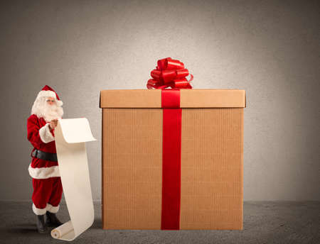 box: Santa Claus with gifts list and a big present box Stock Photo