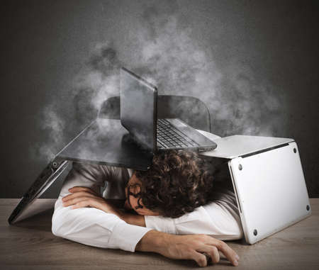 computer problem: Tired businessman sleeping under a pile of computers Stock Photo