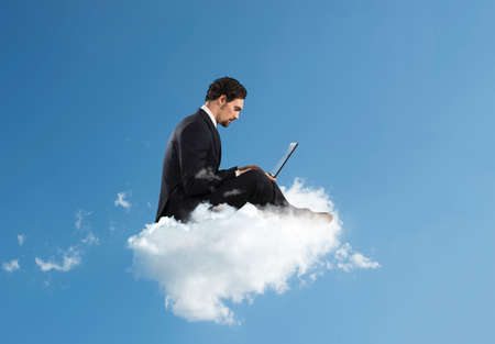 Businessman with laptop on a cloud in the sky. Internet and social network concept Stockfoto