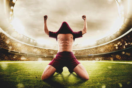 Football player exults in a stadium with audience