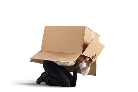 discredit: Afraid businessman is hiding under a cardboard Stock Photo