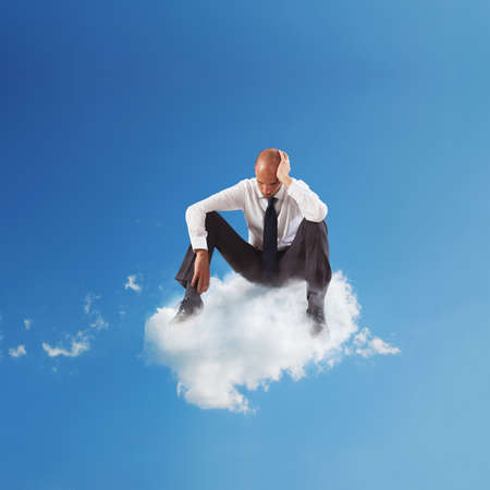 Alone desperate businessman sitting on a cloud in the sky