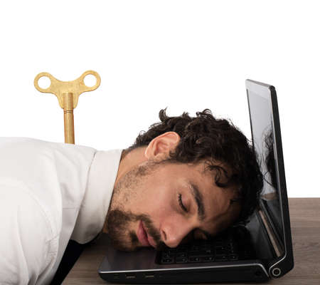 Businessman exhausted from overwork sleeping over computer Stock Photo