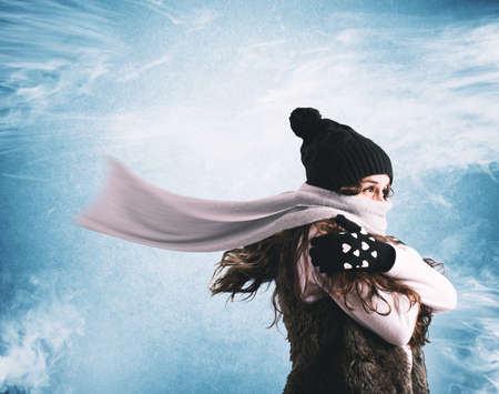 Woman with woolen scarf and hat trying to shelter from the winter cold