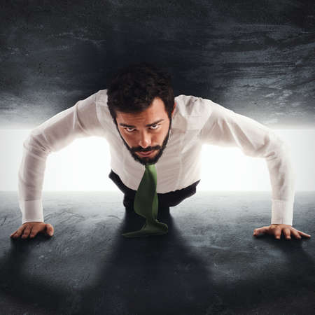 Businessman man trapped between two walls strives to push