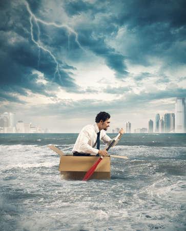 Zakenman surft op een karton tijdens de storm