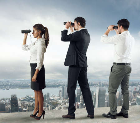 problem: Business people looks at the city from the roof with binoculars Stock Photo