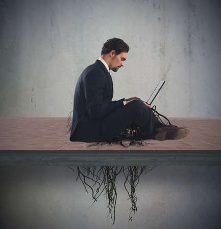 laptop: Businessman sitting with his laptop with roots under