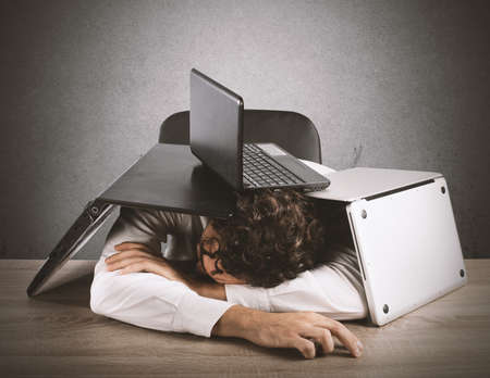 office desk: Tired businessman sleeping under a pile of computers Stock Photo