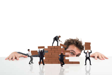project: Businessman watches a teamwork of businesspeople work together by building a brick wall Stock Photo