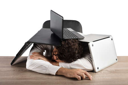 Tired businessman sleeping under a pile of computers Stock Photo