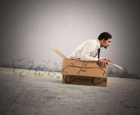 Creatieve man rijden en speelt met zijn kartonnen auto