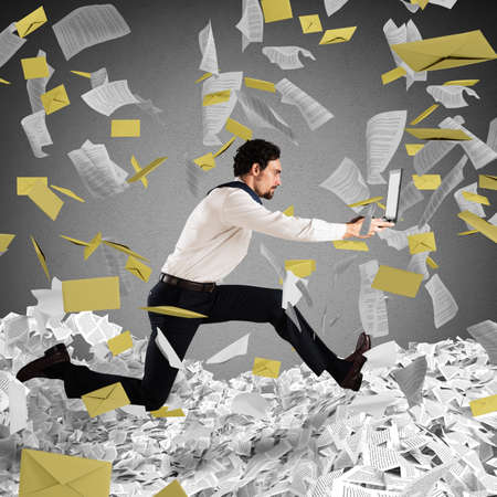 trapped: Businessman with laptop runs away from a paperwork and bureaucracy Stock Photo