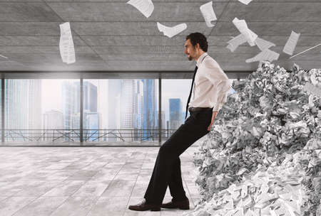 frustrate: Businessman pushing with fatigue a big pile of paperwork Stock Photo