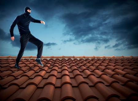 泥棒を着て黒の家の屋根の上を歩く 写真素材