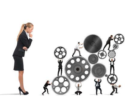 Businesswoman regarde un travail d'équipe de travail de gens d'affaires ensemble à un système d'engrenages