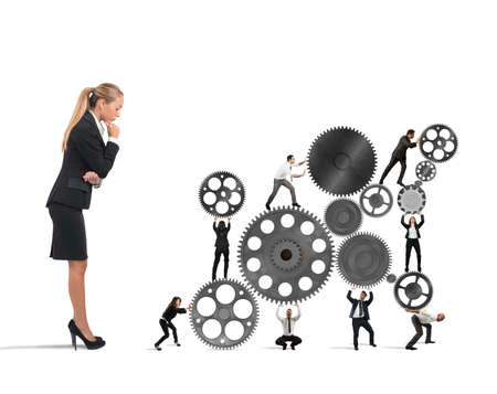 spinning: Businesswoman watches a teamwork of businesspeople work together to a system of gears