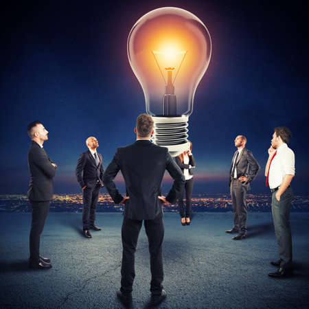 Team of businesspeople watch a big lightbulb
