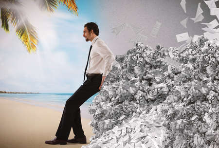 disarray: Businessman pushing with fatigue a big pile of paperwork Stock Photo