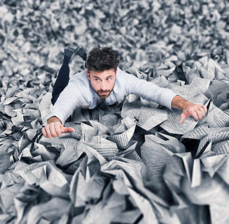 tired businessman: Businessman trying to escape from a pile of paperwork
