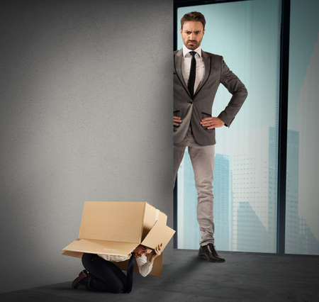 powerless: Employed afraid hides in a box from his big boss