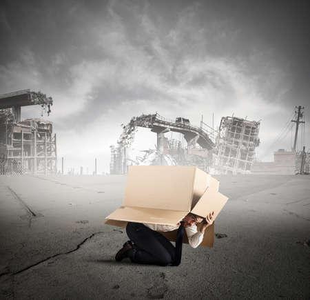 problem: Afraid businessman is hiding under a cardboard in a city destroyed