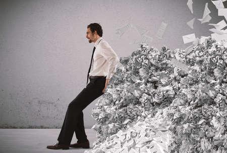 Zakenman duwen met vermoeidheid een grote stapel papierwerk