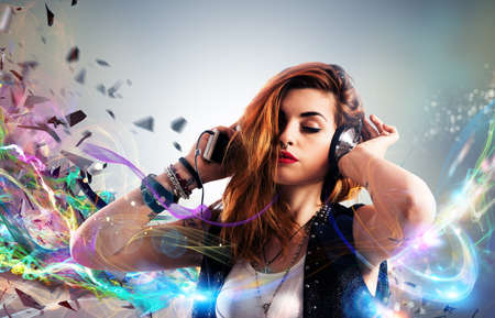 Girl listening to music with headphones on bright colored streaks background Stock Photo