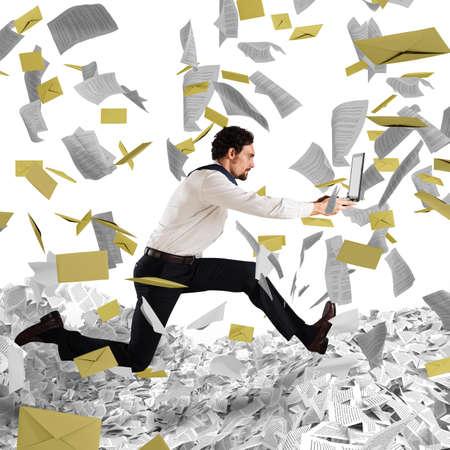 sheet: Businessman with laptop runs away from a paperwork and bureaucracy Stock Photo
