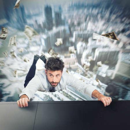 落下を避けるために高層ビルの端に保持している実業家