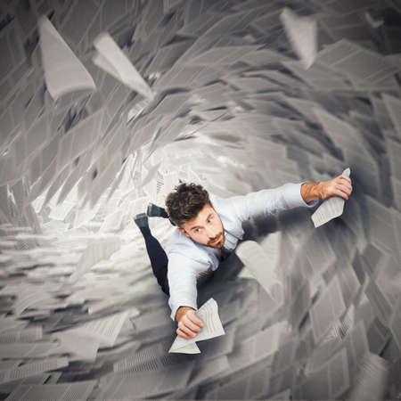 Homme d'affaires tenant à des morceaux de papier qui vont à la baisse