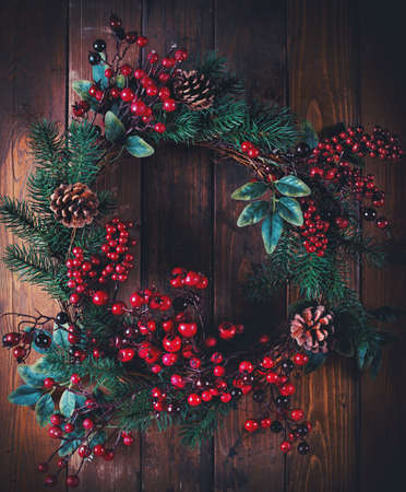 decorate: Christmas wreath decoration with pine cones and hawthorn berries on wooden background
