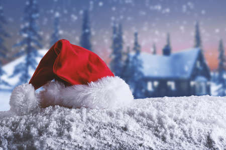 xmas background: Red velvet Christmas hat of Santa Claus on the snow